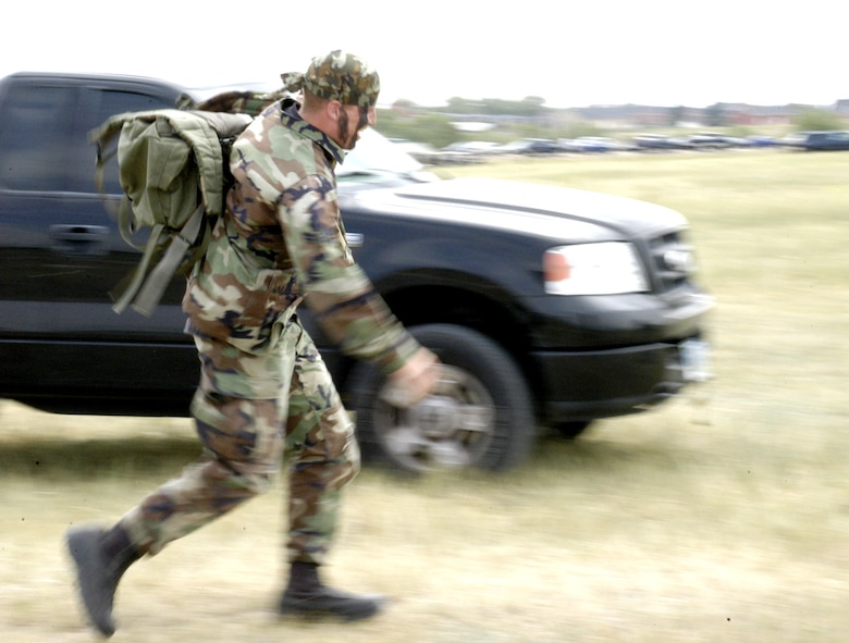 Airman 1st Class Bill Rhodes, 90th Security Forces Squadron, rushes toward the finish line with a sandbag-filled rucksack in an effort to beat the clock. This event tested the physical strength and agility the Airmen possess (Photo by Airman Alex Martinez).