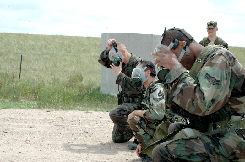 Members of the 90th Security Forces Squadron don gas masks while participating on the ruck-march portion of Crow Creek Challenge. The task included a quarter-mile run and four rucksacks at the end with varying weights. The contest was considered complete when the rucksacks returned safely to the starting line (Photo by Airman 1st Class Daryl Knee).