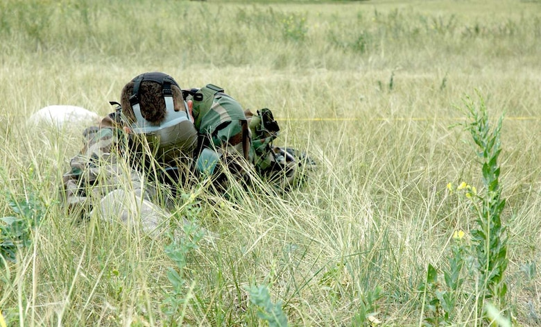 Senior Airman Daren Marshall, 790th Missile Security Forces Squadron, searches blindly for an ammo box in the surrounding area. Members of the team were required to low crawl while patrolling the roped-off section (Photo by Airman 1st Class Daryl Knee).