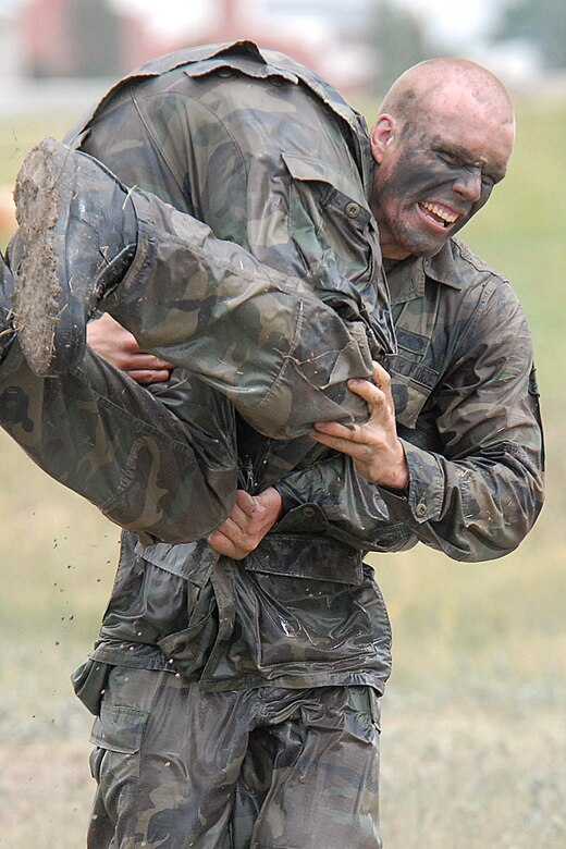 Airman Andrew Vautrin, 90th Security Forces Squadron, carries one of his teammates in a fireman carry during this year's Crow Creek Challenge June 27 at the training complex. Airman Vautrin's team took 2nd place out of 21 teams (Photo by Shelley Raffl).