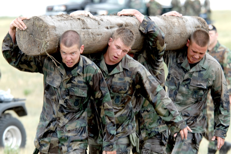 "Airman 1st Class Thomas Peterson, Senior Airman Cliff Howie, Senior Airman Richie Phillips and Airman Ryan White, all of the 790th Missile Security Forces Squadron, carry a log during one of the ""Team Pain"" events (Photo by Shelley Raffl)."