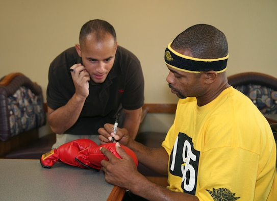 Left, SSgt Joshua Cubero, 334 Training Squadron, receives an autograph from professional boxer Roy Jones Jr. on July 4 at the Magnolia Dining facility.  (U.S. Air Force photo by SMSgt Dean Ross)