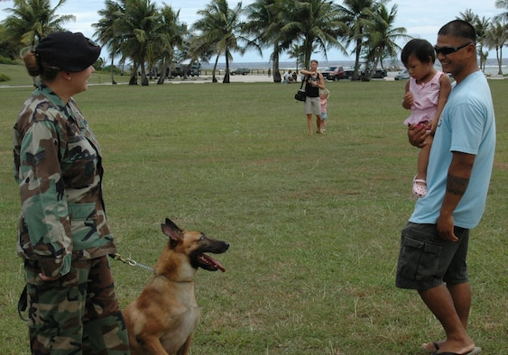 Senior Airman Darlene Donoho, 36th Security Forces Squadron, shows her dog to Kenneth and Cloey Ray TedTaoTao during the pre-Liberation Day military expo at Asan Beach July 7. Several units from Andersen were represented to help familiarize the local community with Andersen's mission. (U.S. Air Force photo by Capt. Joel Stark)