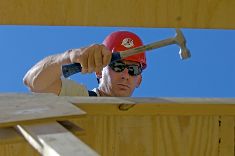 """Tech. Sgt. Chris Belknap adjusts the spacing between roof trusses June 22 at at Forward Operating Base Kalsu, Iraq. Sergeant Belknap is the site foreman with the 557th Expeditionary RED HORSE Squadron, one of the Rapid Engineer Deployable Heavy Operational Repair Squadron Engineers, or RED HORSE, Airmen who are forward deployed from Balad Air Base, Iraq and tasked to build four tactical operations centers for the Army's 2nd Brigade combat team, 3rd Infantry Division headquartered here. The 2/3 ID is currently running operations out of tents. The RED HORSE unit, made up of Air Guard, Reserve and active-duty Airmen, was requested by the Army to come into this """"Triangle of Death"""" location because of their self-suffiency and for the multiple skill sets they bring to a project. (U.S. Air Force photo/Master Sgt. Jim Varhegyi)"""