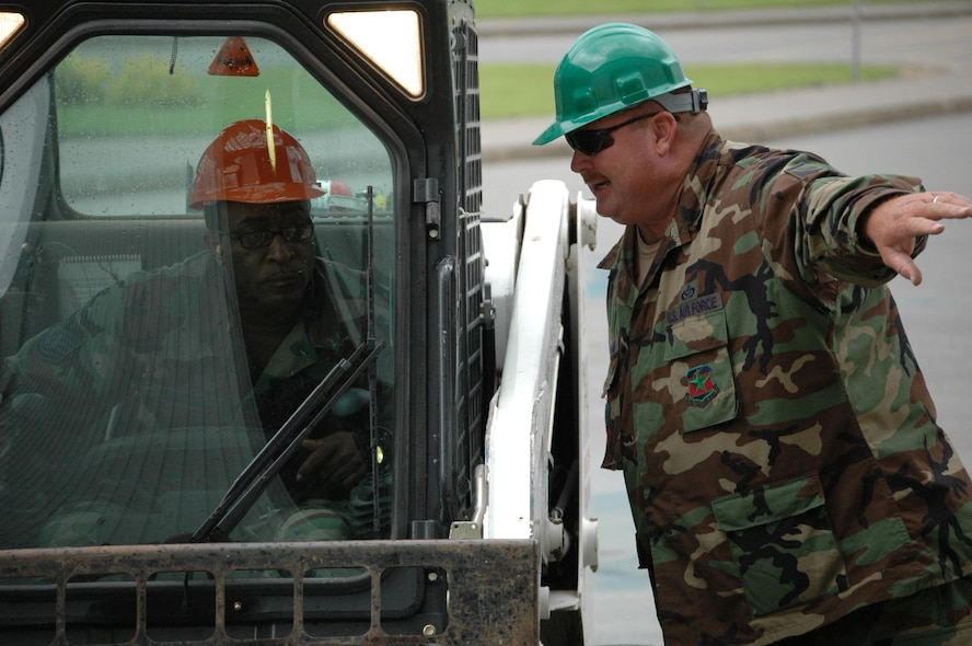 """Master Sgt. Tim """"Bull"""" Durham (right) provides guidance to Technical Sgt. Rodney Blanton as Sergeant Blanton prepares to drive a Bobcat on site in Moose Jaw. (Texas National Guard photo/Senior Master Sgt. Marcus Falleaf)"""