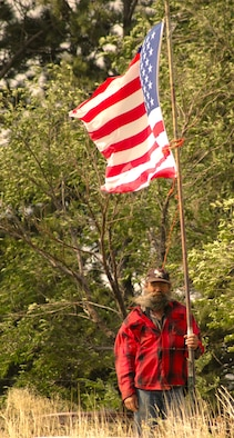 COLORADO SPRINGS, Colo. -- Jack Weber stands next to his flag near his property on Highway 94 and Curtis Road. Mr. Weber makes sure there's always a flag displayed outside in honor of the troops. (U.S. Air Force photo/Lorna Gutierrez)