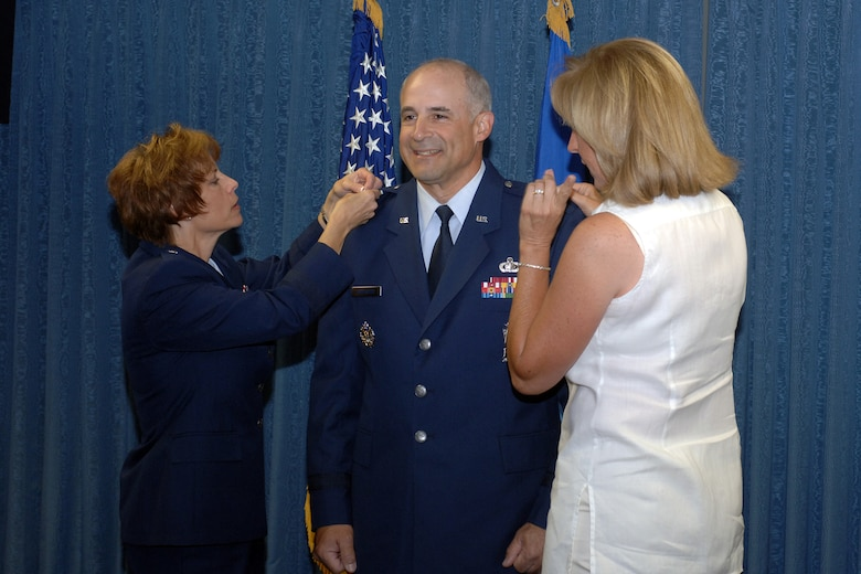 HILL AIR FORCE BASE, Utah--Colonel Kenneth Merchant, vice commander for the Ogden Air Logistics Center, gets his brigadier general star pinned on by Brigadier General Kathleen Close, Ogden ALC commander, and his wife Sue during a promotion ceremony held in his honor July 3. (U.S. Air Force photo by Alex R. Lloyd)