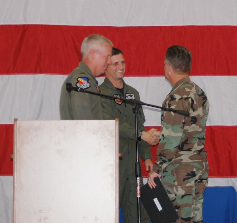 Col. Robert Beletic shakes hands with Col. Scott Chambers, 75th Air Base Wing commander, at Col. Beletic's farewell in Hangar 37 June 29 while Col. Todd Harmer looks on.