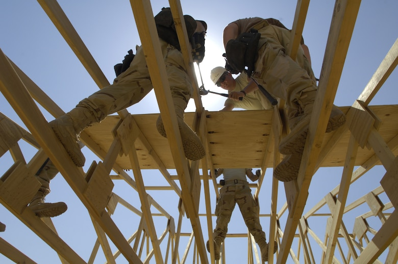 "FORWARD OPERATING BASE KALSU, Iraq -- U.S. Air Force Airmen with the 557th Expeditionary RED HORSE Squadron, work on the roof of a tactical operations center June 22, 2007. The Rapid Engineer Deployable Heavy Operational Repair Squadron Engineers RED HORSE Airmen are forward deployed from Balad Air Base, Iraq, and are tasked to build four tactical operations centers for the Army's 2nd Brigade combat team, 3rd Infantry Division headquartered here. The 2/3 ID is currently running operations out of tents. The Air Force RED HORSE unit, made up of Air Guard, Reserve and active duty Airmen, was requested, by the Army, to come into this ""Triangle of Death"" location because of their self-suffiency and for the multiple skill sets they bring to a project. Besides the TOCs the RED HORSE Airmen are working on several other projects at the FOB. (U.S. Air Force photo/Master Sgt. Jim Varhegyi)"