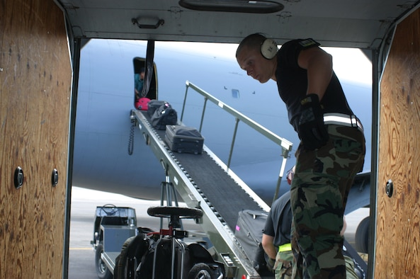 HICKAM, Hawaii - Senior Airman Dustin Weidner and Tech. Sgt. Marshall Palmer, passenger services specialists with the 87th Aerial Port Squadron deployed from Wright-Patterson AFB, Ohio, load baggage onto a KC-135 using a baggage conveyor. (U.S. Air Force photo/Master Sgt. Doug Moore)
