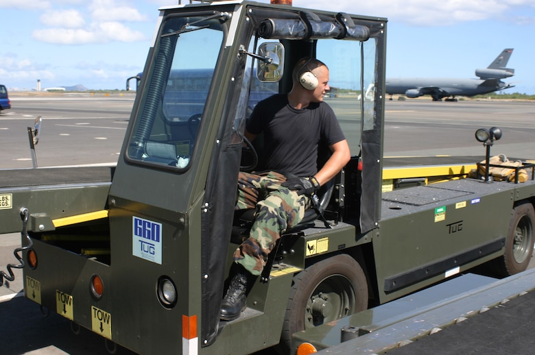 HICKAM AFB, Hawaii - Senior Airman Dustin Weidner, a passenger services specialist with the 87th Aerial Port Squadron deployed from Wright-Patterson AFB, Ohio, drives a baggage conveyor to load baggage on a KC-135. (U.S. Air Force photo/Master Sgt. Doug Moore)