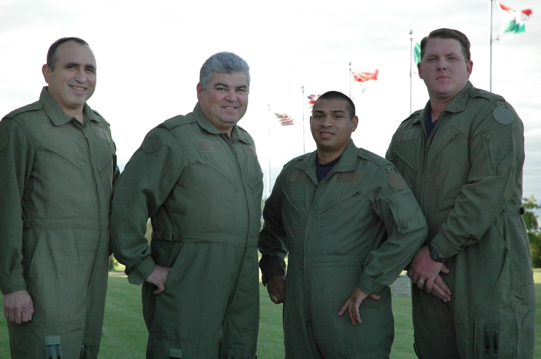 Country flags fly above the heads of civil engineer squadron members (L-R) Senior Airman Albert Champion, Staff Sgt. Otto Adkins, Senior Airman David Luna and Staff Sgt. Cole Martin wearing flight suits in preparation for incentive rides. (USAF Photo/Senior Master Sgt. Marcus Falleaf)