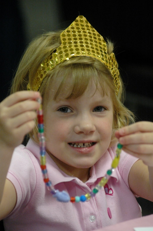 Cameron Owens, 4,shows off the  jewelry she created with beads at Princess Camp.  U. S. Air Force photo by Sue Sapp