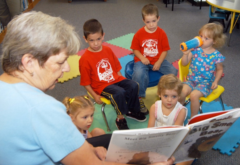 """Blanchella Casey, supervisory librarian, reads the book, """"Big Smelly Bear"""" to preschool children at the library July 2. U. S. Air Force photo by Sue Sapp"""