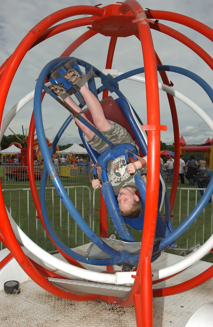 Strapped in and secure, 8-year-old Riley Naylor, son of Suzanne and Col. Richard Naylor, 37th Training Group commander, takes a spin in the patriotic-colored Space Ball during the 2007 Star Spangled Festival at Lackland Air Force Base, Texas, on Independence Day. (USAF photo by Alan Boedeker)