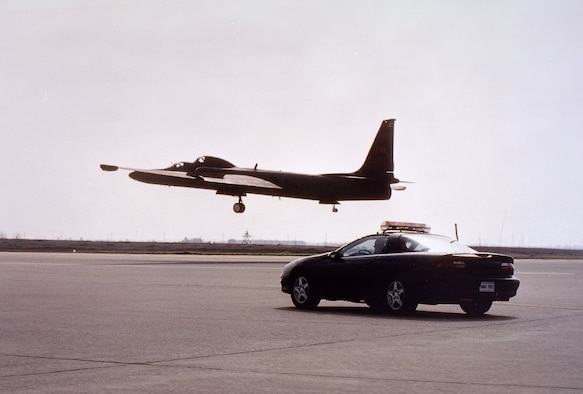 Dual cockpit TU-2S, the training version of the U-2 in which the instructor sits behind the student, being followed down the runway during landing by a chase car. (U.S. Air Force photo)