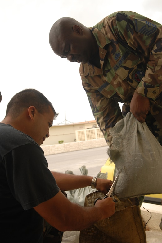 Master Sgt. Lawrence Armstrong (standing) and Staff Sgt. Victor Matus refill sandbags for their building at Kadena Air Base, Japan on July 12, 2007. The sandbags are being filled in preparation of Typhoon Man-Yi, the first typhoon of the year for the base. Both are assigned to the Electronic Warfare Section of the 353rd Maintenance Squadron. U.S. Air Force photo/Staff Sgt. Chrissy FitzGerald