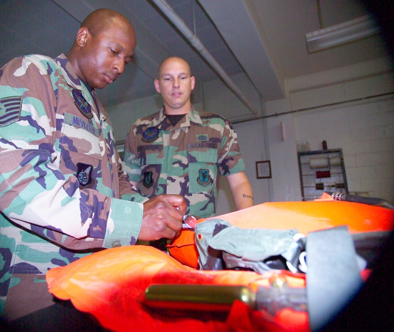 Staff Sgt. Richard Bystrzycki, right, shows Tech. Sgt. Timothy Middleton, left, maintenance procedures on a life preserver unit during cross training into the new aircrew flight equipment career field at the 18th Operations Squadron Kadena Air Base, Japan. U.S. Air Force/Scott Hallford