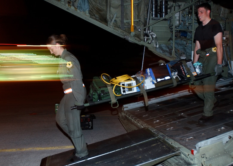 Staff Sgt. Erin Reifer and Senior Airman Kiley Gervitsen from the 18th Aeromedical Evacuation Squadron, Kadena Air Base, Japan, simulate evacuating casualties from a C-130 Hercules in Marine Corps Air Station Futenma, Japan, in preparation for Air Mobility Rodeo 2007. The unit practiced in the evenings to simulate night time operations for wartime missions. U.S. Air Force photo/Staff Sgt. Reynaldo Ramon