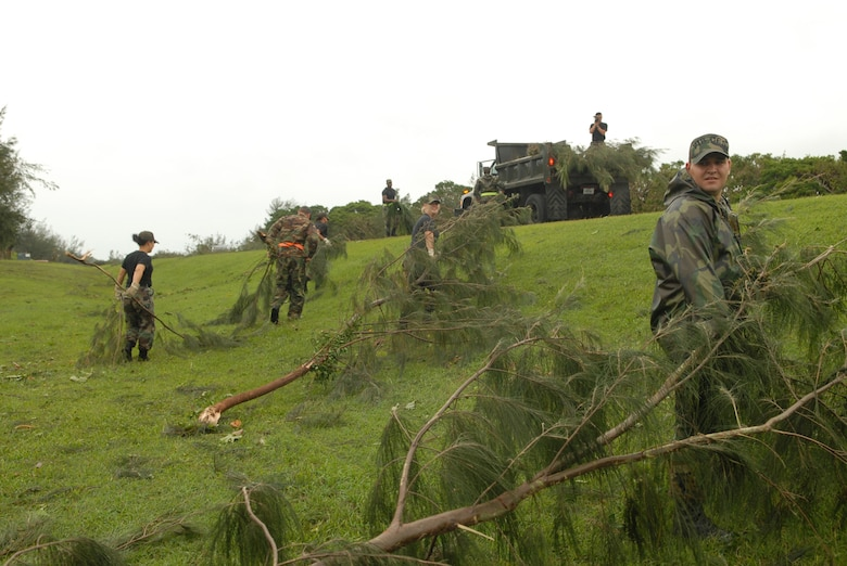 Airmen from the 18th Civil Engineer Group gather tree branches into a pile at Kadena Air Base, Japan, July 14, 2007. The branches were knocked down by Typhoon Man-Yi which brought the base 77 mph winds gusting to 105 mph.  There were no injuries or significant damages to base structures.  The typhoon was the strongest to hit the base since 2003.  Both Airmen are assigned to the 18th Civil Engineer Squadron.  U.S. Air Force Photo/Staff Sgt. Chrissy FitzGerald