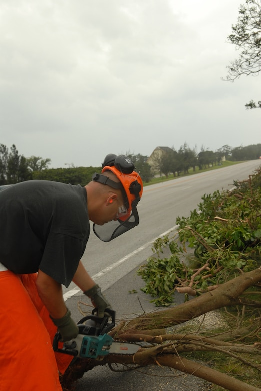 Tech. Sgt. John Platz cuts large downed branches with a chainsaw  at Kadena Air Base, Japan, July 14, 2007. The fallen branches were a result of Typhoon Man-Yi which brought the base 77 mph winds gusting to 105 mph.  There were no injuries or significant damages to base structures.  The typhoon was the strongest to hit the base since 2003.  Sergeant Platz is an equipment operator with the 18th Civil Engineer Squadron.  U.S. Air Force Photo/Staff Sgt. Chrissy FitzGerald