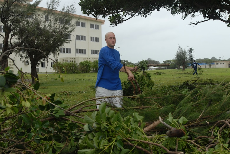 Senior Airman Matthew Amerson piles tree branches outside his dormitory at Kadena Air Base, Japan, July 14, 2007. The branches were knocked down by Typhoon Man-Yi which brought the base 77 mph winds gusting to 105 mph.  There were no injuries or significant damages to base structures.  The typhoon was the strongest to hit the base since 2003.  Airman Amerson is assigned to the 18th Logistics Readiness Squadron.  U.S. Air Force Photo/Senior Airman Darnell T. Cannady
