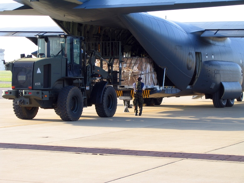 """An Airman with the New Zealand Air Force uploads pallets onto a C-130 with the help of 452nd Air Mobility Wing Airmen from March Air Reserve Base. Five members from the 452nd Tanker Airlift Control Element at March ARB went to Fort Polk, La., to participate in a Joint Readiness Training Exercise last month. They spent ten days training with two air movement crews from the New Zealand Air Force who were participating in simulated desert combat training scenarios. With the use of a C-130 from New Zealand's Hercules aircraft fleet, the reservists from March helped train their international counterparts through various exercises to include day and night air drops and combat on-and off-loading. Under the JRTC training scenario, the TALCE from March was also receiving command and control training through a variety of separate scenarios being thrown at them. (U.S. Air Force photo's by Roughsedge """"Skip"""" Higginson)"""