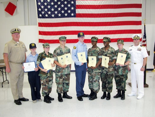 Sea Cadet Lt. j.g. Tom Blackshear (left), Commanding Officer, US Naval Sea Cadet Corps, and Cmdr. Steven Hartsel, Commanding Officer, Navy Operational Support Center Moreno Valley at March Air Reserve Base, took time June 24 to recognize several cadets from the corps for various achievements. The recipients were (from second to left) Arianna Prather - US Navy certificate for painting US Vets, a veterans home here at March Field; Christa Zard- US Navy certificate for painting US Vets, a veterans home here at March Field and first year ribbon; Aaron Nugent- first year and recruiting ribbon; Alex Saunders- Presidential Physical Fitness Ribbon Award; Latesa and Larissa McKinney- second year ribbon; Katie Magnone- academic achievement ribbon. (U.S. Air Force photo by Staff Sgt. Joe Davidson)