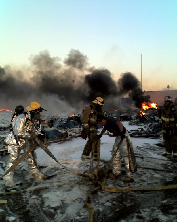 Several March Air Reserve Base firefighters move hoses after containing the fire. (U.S. Air Force photo by Chris Christianson)
