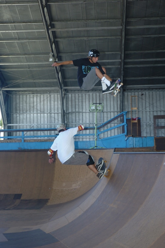 Chris Kays gets a front-side air over his dad Mike in one of two 'bowls' at Hickam's Sk8 Park. Anthony Eischens, 8, jumps from one ramp to another. Photo by Mark Munsey