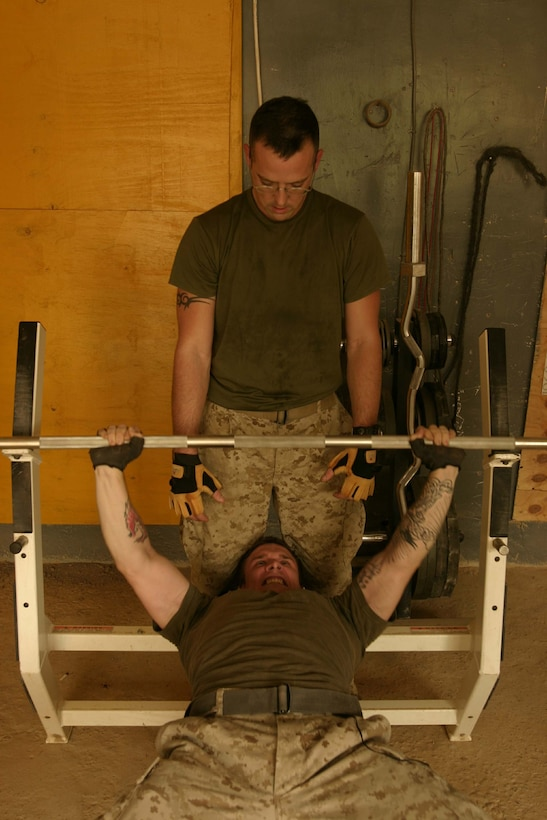 HADITHA, Iraq ? Staff Sgt. John Wear, staff noncommissioned-officer-in-charge of the Intelligence section, Headquarters and Service Company, Task Force 1st Battalion, 3rd Marine Regiment, Regimental Combat Team 2, assists a fellow Marine with his bench press in the gym located in the Hadithah forward operating base.