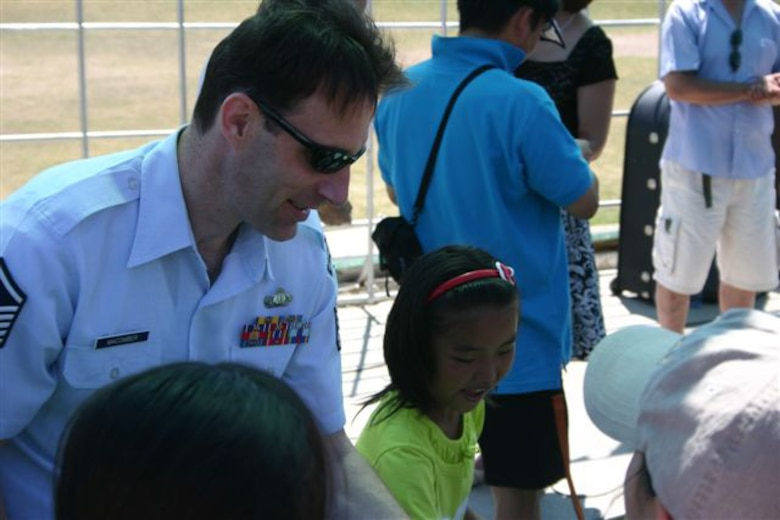 "ULAANBATAAR, Mongolia -- Master Sgt. Dean McComber of the USAF Band of the Pacific-Asia interacts with a student from the International Children's Centre ""Nairamdal"" (youth camp) July 4."