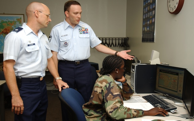 Lt. Col. Mark Mesenbrink, left, 335th Training Squadron commander, is briefed by  Master Sgt. Robert Marlett, 335th TRS instructor supervisor, on the combat weather team operations course.  The student is 1st Lt. Martine Morris.  Colonel Mesenbrink took command of the 335th TRS from Lt. Col. Elia Sanjume July 12.  (U.S. Air Force photo by Kemberly Groue)