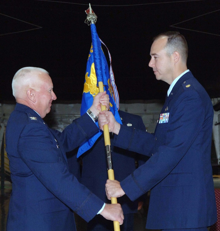 WHITEMAN AIR FORCE BASE, Mo. - Col. Bob Dulong, 509th Maintenance Group commander, passes the guidon of the 509th Aircraft Maintenance Squadron to Maj. Richard Gibbs during a change-of-command ceremony July 12. Major Gibbs was previously assigned to the Naval War College in Newport, R.I. Lt. Col. Kevin Gulden, the former 509th AMXS commander, moves on to Ellsworth Air Force Base, S.D., and becomes the 28th AMXS commander. (U.S. Air Force photo/Staff Sgt. Felicia Haecker)