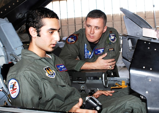 "Maj. Jack Fischer (right), 411th Flight Test Squadron F-22 Raptor pilot, explains the different controls in an F-16 Fighting Falcon cockpit to Avi Khanian (left) during the ""Pilot for a Day"" tour here July 12. As a pilot for the day, 14-year-old Avi received an opportunity to see Edwards' various aircraft including the CV-22, F-22A, F-16 and the Global Hawk. The program was sponsored by the base's Company Grade Officer Council. Avi has undergone treatment at Mattel Children's Hospital in Los Angeles for Ewing's sarcoma, a form of bone cancer often found in children. (Photo by Jim Shryne)"