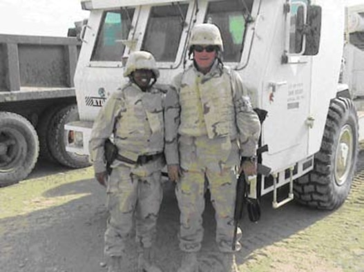 First Lieutenant Shawntara Govan and Mr. William Lewis, of AFRL's Materials and Manufacturing Directorate, stand in front of remote-controlled Mine Area Clearance Equipment at Bagram Air Base, Afghanistan.
