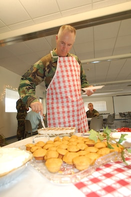 Chief Master Sgt. Kevin Soltis, 412th Test Wing command chief, prepares food during a free home-cooked meal for dorm dwellers July 12 at Chapel 1. Organizations such as the Edwards spouses clubs, Commissary and Club Muroc provided support for the event. (Photo by Airman 1st Class Julius Delos Reyes)