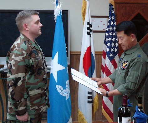 Brigadier General Kwon, Oh Sung commander 1st Fighter Wing, Republic of Korea Air Force(Right) presents Major Jason K. Humphrey commander, detachment 1, 607th materiel maintenance squadron(Left) with a Letter of Commendation for the meritorious efforts that he and the detachment have rendered to the 1st Fighter Wing.  Major Humphrey hosted a friendship dinner for the ROKAF 1st Fighter Wing leadership and the 607th Air Support Group.  The dinner was held at the Detachment 1's recreation center at Gwang Ju Air Baseon 12 July, 2007.  (Courtesy Photo)