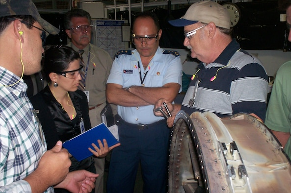 Jack McSwain, 548th Propulsion Maintenance Squadron welding supervisor, explains the oil tube welding process to Turkish welding engineer Burcu Okur during a visit July 9 and 10. Looking on are, from left, Darren Raines, 548th PMXS welder; Larry Waite, Turkish program manager with the 748th Combat Sustainment Group; and Lt. Col. Tolga Yidiz, Turkish air force liaison. (Air Force photo by 2nd Lt. Eric Scott)