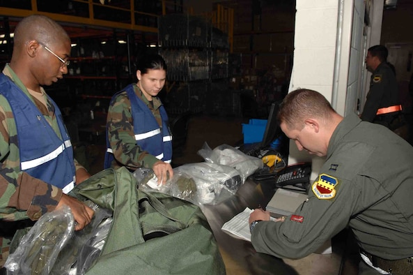 SHAW AIR FORCE BASE, S.C.-- Staff Sgt. Michael Henry, 20th Communications Squadron project manager, and Airman 1st Class Elizabeth Mclean, 20th Services Squadron food services technician, issue chemical warfare gear to Capt. Daniel McAffe, 77th Fighter Squadron, during a Phase I operational readiness exercise at the Chandler Deployment Processing Center July 16.  Operational readiness exercises are a training tool to help prepare Airmen for pre-deployment and deployment mission requirements. (U.S. Air Force Photo/Staff Sgt. Henry L Hoegen Jr.)