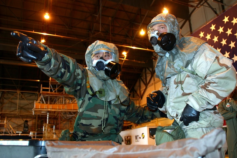 Airman 1st Class Chris Reyburn and Airman Christian Sousa, 552nd Air Maintenance Squadron, read over a step-by-step sign while going through the chemical decontamination line during the ATSO Rodeo challenge. (Air Force photo by Senior Airman Lorraine Amaro)