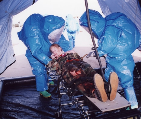 "Tinker personnel decontaminate a ""victim"" during a recent weapons of mass destruction exercise involving outside agencies. Adopting the Air Force Incident Management System, based on the National Incident Management System and National Response Plan, now allows Tinker emergency responders to better communicate with their civilian counterparts in a crisis situation. (Air Force photo)"