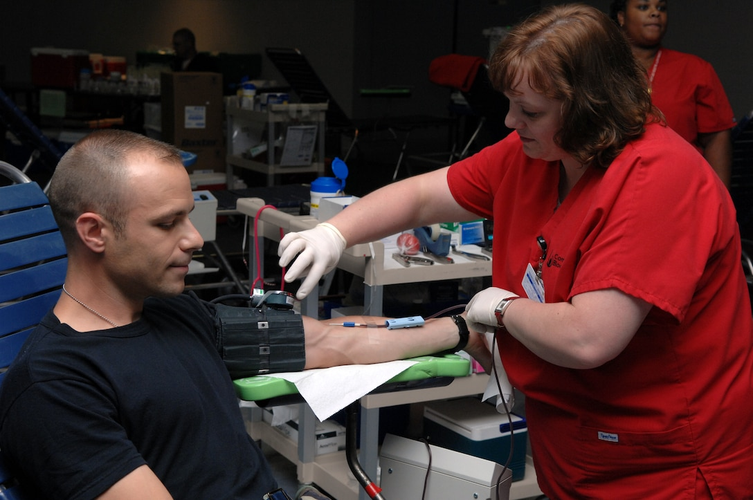 WHITEMAN AIR FORCE BASE, Mo. -- Grace Gibony, a phlebotomist for the Community Blood Center monitors Maj. Ryan Girrbach, 509th Medical Group, as he gives blood at the community activities center July 19. The Community Blood Center distributes 550 pints of blood a day to more than 70 hospitals in the area. Blood is tested within 24 hours of donation and sent to a hospital within 48 hours. It has a shelf life of 42 days. Blood collected by the Community Blood Center is used within five days of collection, according to Carolyn Garner, a Community Blood Center representative. (U.S. Air Force photo/Airman 1st Class Stephen Linch)