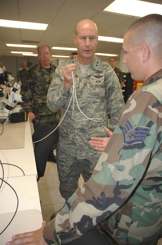 Maj. Gen. Douglas L. Raaberg, the director of air and space operations at Headquarters Air Combat Command, Langley Air Force Base, Va., holds up a power cord for the Blue Force airborne tracking system and talks with Staff Sgt. Robert Brutto, an AFREP technician here, about how it was repaired. General Raaberg stopped by the AFREP shop during his visit to D-M this week. (U.S. Air Force photo/Staff Sgt. Jake Richmond)