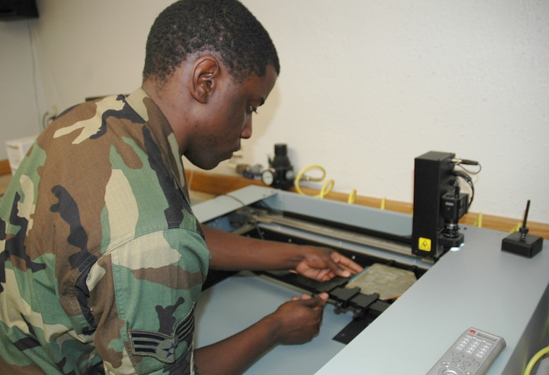 Senior Airman Torry Murray, an AFREP technician here, aligns a malfunctioning circuit card assembly into a troubleshooting card reader. Using a database that includes specifications for various circuit cards in use throughout the military, the machine runs diagnostic tests and reveals the cards' problems to the maintainers. (U.S. Air Force photo/Staff Sgt. Jake Richmond)