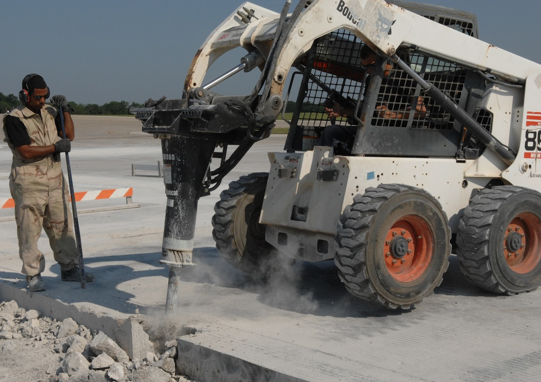 WHITEMAN AIR FORCE BASE, Mo. -- Staff Sgt. Derek Phillips, 823rd RED HORSE Squadron, stands by as Senior Airman Zachary Norris, 823rd RHS, uses a Bobcat to demolish a concrete slab. (U.S. Air Force photo/Staff Sgt. Jason Barebo)