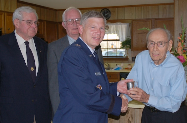 "Lt. Gen. Robert J. Elder Jr., Eighth Air Force commander, accepts the donation of one of the nine Eaker Bowl cups from Mr. Charles Jones Jr. on Thursday, June 5th. Mr. Jones' father, Lt. Col. (ret.) Charles Jones Sr., was one of the nine original members of the famous Castle Coombe Mess.  General Ira C. Eaker, who first commanded Eighth Air Force in England during World War II, established the Castle Coombe Mess, which purchased the Eaker Bowl and cups with the optimistic vision of conducting post-war reunions. The donation of the cup by Mr. Jones, who also served in World War II, is the fifth silver cup donated to Eighth Air Force, with the remaining four cups kept by the respective family members as a cherished memento of their link to World War II history. General Elder was accompanied by two former Eighth Air Force commanders, Lt. Gen. (ret.) E.G. ""Buck"" Shuler Jr. and Lt. gen. (ret.) Edgar S. Harris Jr., who originally accepted the donation of the bowl, ladle, and his cup from General Eaker in 1981. The Eaker Bowl is a physical piece of the Mighty Eighth's history which occupies a place of honor at Eighth Air Force headquarters as a heraldic symbol of sterling service to the nation, comradeship, and optimism about the future by those who have served with The Mighty Eighth. (U.S. Air Force Photo by Capt. Rob Goza)"