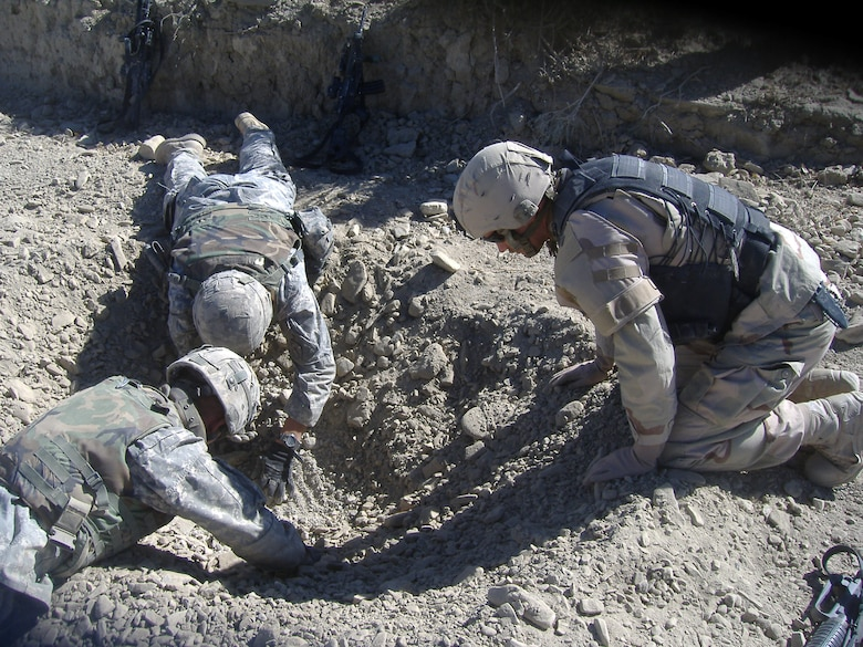 Staff Sgt. Matthew Nuckolls and some Soldiers he was working with examine a crater in Afghanistan for forensic evidence. Sergeant Nuckolls is one of eight members of Peterson's Explosive Ordinance Detachment who have recently deployed to Iraq and Afghanistan. (U.S. Air Force photo)