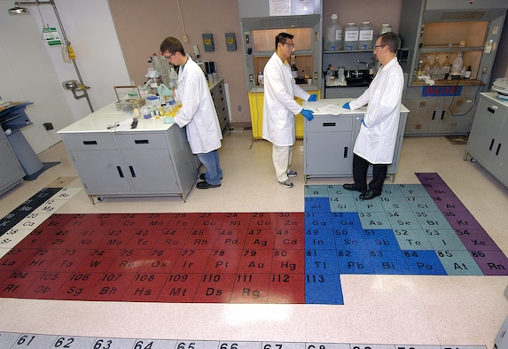 A colorful periodic table now graces the floor of the 76th Maintenance Wing Electroplating Lab, an idea of chemist Chris Mance, right, who did the work with help from chemist David Nguyen, center. Fellow chemist Carson Cameron, left, works in the open design that also now allows easier access to an emergency eye wash station. (Air Force photo by Margo Wright)
