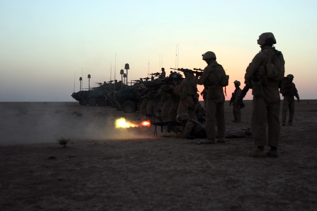 COMBAT OUTPOST RAWAH, IRAQ, -- Fire erupts from the barrel of a squad automatic weapon as Marines and light armored vehicles with Company C, 1st Light Armored Reconnaissance Battalion, Regimental Combat Team 2, line up and fire during combined arms training. The training was part of the first week of Operation Mawtini. Official Marine Corps Photo By Cpl. Ryan C. Heiser.